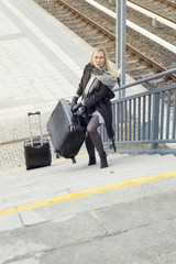 woman with heavy suitcases walking up stairs at train station