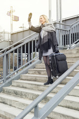 woman with suitcase walking down stairs at train station