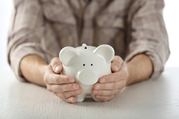 Male hands holding piggy bank at wooden table closeup
