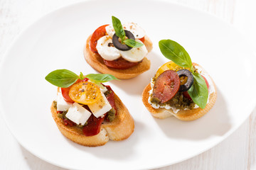 bruschettas with tomatoes and mozzarella on plate, top view