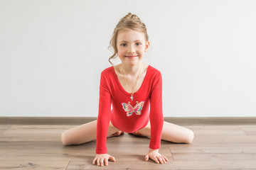 Flexible little girl in red leotard doing gymnastic