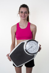 Time to check your weight. Studio shot of a beautiful female holding scales looking surprised isolated on white copyspace on the side