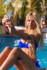 Young pretty blonde woman taking selfie photos in swimming pool