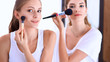 Beautiful girls looking in the mirror and applying cosmetic with a big brush