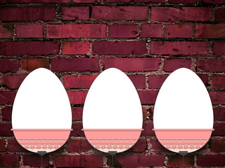 Close-up of three hanged blank Easter egg frames with clips against weathered red brick wall background