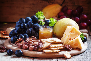 Snack plate: grapes, pears, hazelnuts, almonds, walnuts, cheese