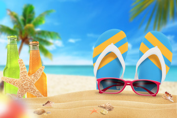 Sunglasses, juice and slippers on beach. Starfish and shells on sand. Beach and sea with palm in background.
