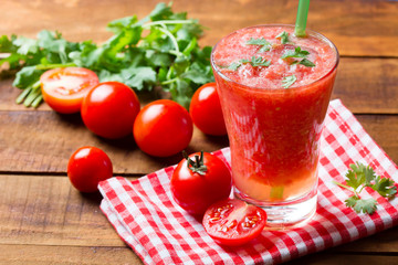 Tomato smoothie on wooden background
