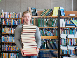 Portrait of a male student with pile books in college library
