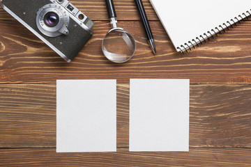 Travel, vacation concept. Camera, notepad, pen, credit card, supplies and photography on office wooden desk table. Top view with copy space for text