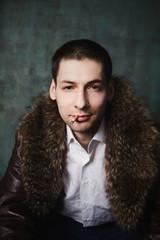 portrait of handsome man in fur coat with cigarette