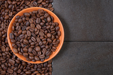coffee beans in an orange plate on a dark stone background