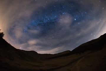 180 degree view of the starry sky and Milky Way on the Alps with blurred motion clouds drawing scenic vortex due to fisheye lens distortion. Some digital noise due to 1600 iso setting.