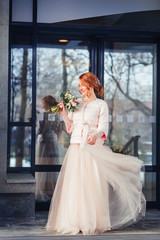 Happy bride on the background of modern urban glass building