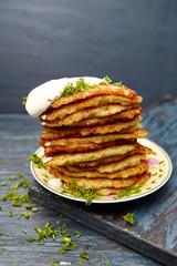 Tower of potato pancakes on a dark background .