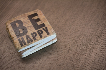 A stone coaster on a wooden table surface reading Be Happy