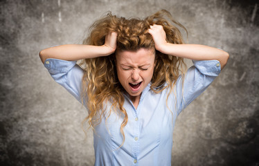 Angry and stressed woman pulling her hair