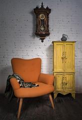 Composition of vintage orange armchair, yellow cupboard, pendulum clock and black scarf