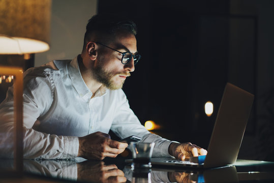 Bearded young businessman working on modern loft office at night. Man using contemporary notebook texting message, holding smartphone, blurred background. Horizontal, film effect.
