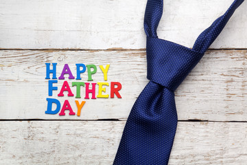 Happy fathers day sign and tie laid on wood