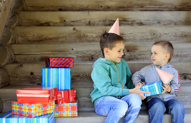 many gifts on the child's birthday. children's birthday party. brothers going to unwrap gifts