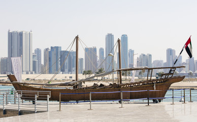monument of old boat and skyscrapers on background in united emirates