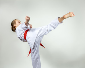 Young girl in a kimono with a red belt makes kicking karate