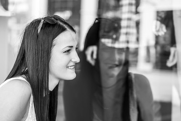 Beautiful girl looking in the shopwindow, black and white photography