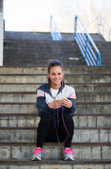 Beautiful hispanic woman listen music after running
