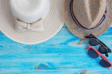 Summer hats  and sunglasses on blue wooden background