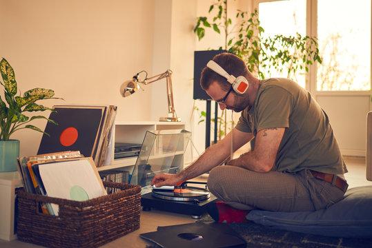 Male choosing next vinyl record to play. Audiophile gramophone.
