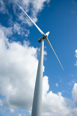 White wind turbine in vertical composition against blue sky and white clouds.