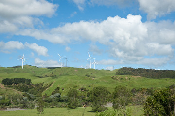 Rural New Zealand with white wind turbines on high points.