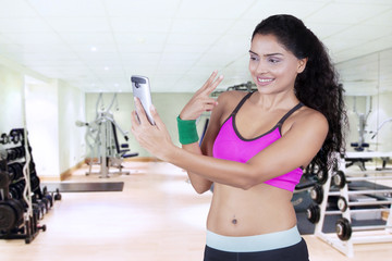 Young athlete taking selfie photo at gym
