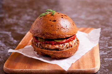 Sandwich with chicken burger, tomate souce and pickled cucumber