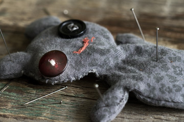 Voodoo doll and pins on old vintage wooden floor