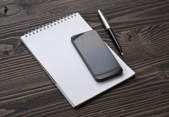 On the desktop the smartphone, notebook with pen