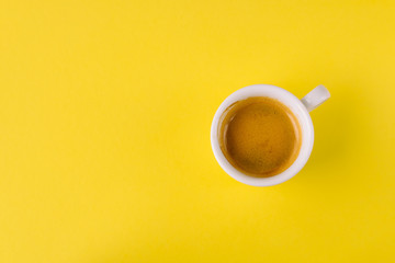 Small cup of coffee on bright yellow background, top view