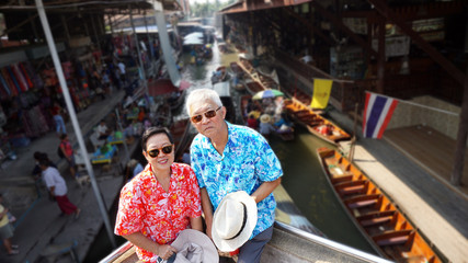 Asian senior couple travel to thailand floating market