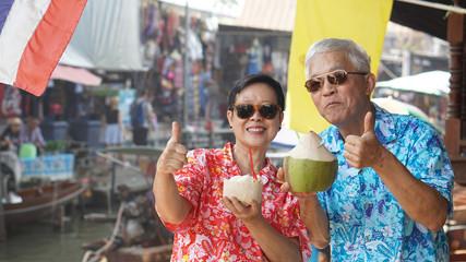 Asian senior couple travel to thailand floating market. Drinking