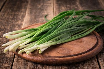 Spring onions also known as salad onions, green onions or scallions on wood background
