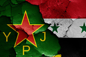 flags of YPJ and Syria painted on cracked wall