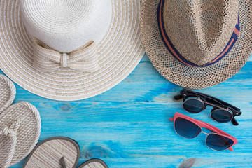 Summer hats  and other travel accessories on blue wooden backgro