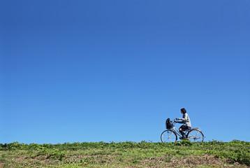 土手を自転車通学をする女子高生