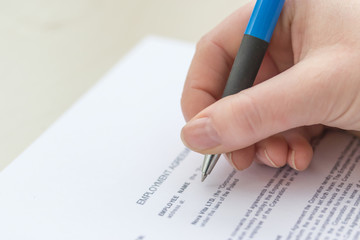 Close Up View of a woman`s  hand filling employment agreement form.