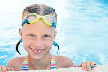 Portrait of little cute girl in the swimming pool. Sunny summer