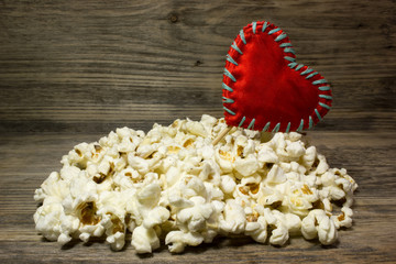 Popcorn and red heart love on wooden background