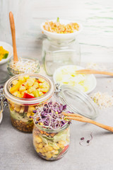 Tasty vegetables salads in jars with corn and  sprouts on light rustic kitchen table, close up.  Healthy lifestyle or diet food concept