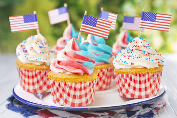 Cupcakes with red-white-and-blue frosting and American flags on