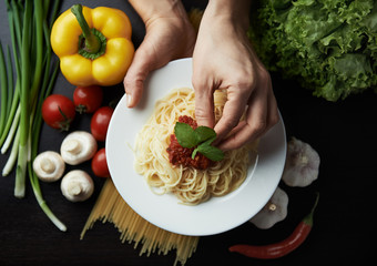 Female chef decorating Italian pasta sauce and basil. Concept of traditional cuisine and healthy meal.